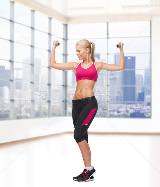 Stock photo: young sporty woman with dumbbells