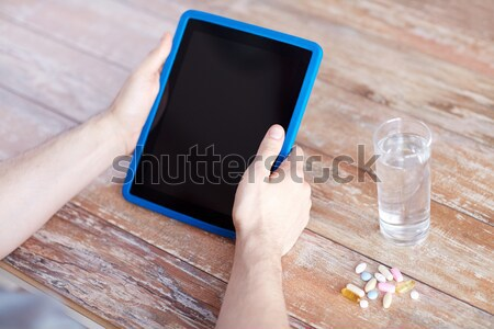close up of hands with tablet pc, pills and water Stock photo © dolgachov