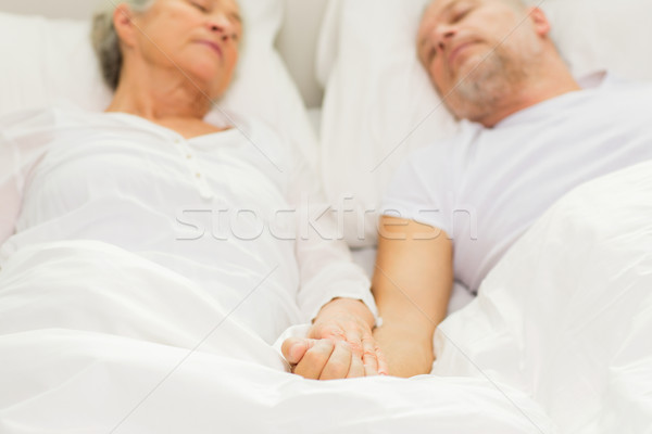 close up of senior couple sleeping in bad at home Stock photo © dolgachov