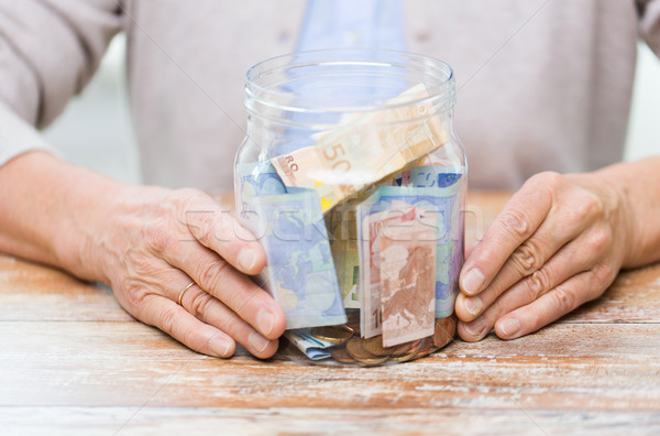 close up of senior woman with money in glass jar Stock photo © dolgachov