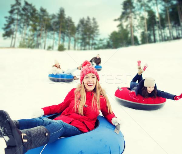 group of happy friends sliding down on snow tubes Stock photo © dolgachov