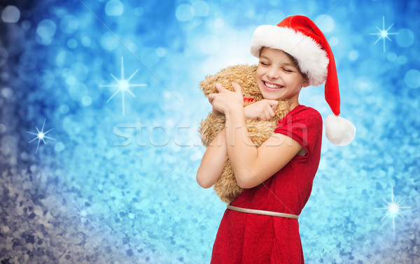 smiling girl in santa helper hat with teddy bear Stock photo © dolgachov