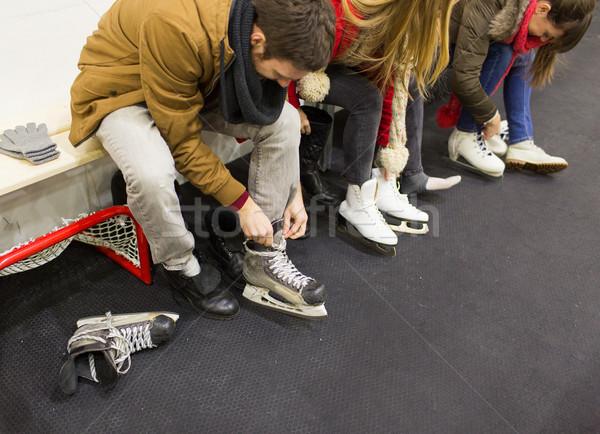 close up of friends wearing skates on skating rink Stock photo © dolgachov