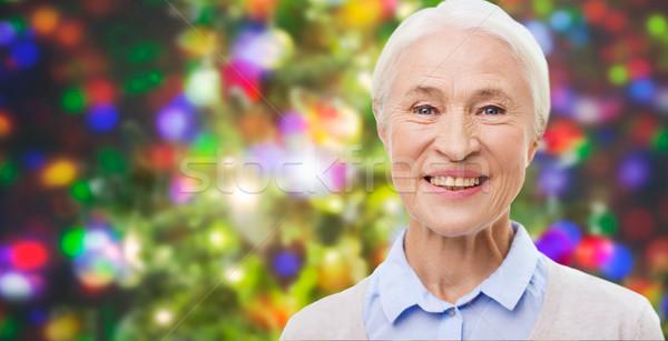 happy senior woman face over christmas lights Stock photo © dolgachov