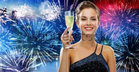 beautiful woman with champagne glass over firework Stock photo © dolgachov