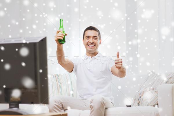 Sorridere uomo guardare tv bere birra Foto d'archivio © dolgachov