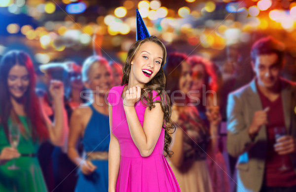 happy woman or teen in party cap at night club Stock photo © dolgachov