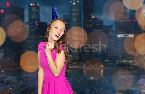 Stock photo: happy young woman in party cap over night city