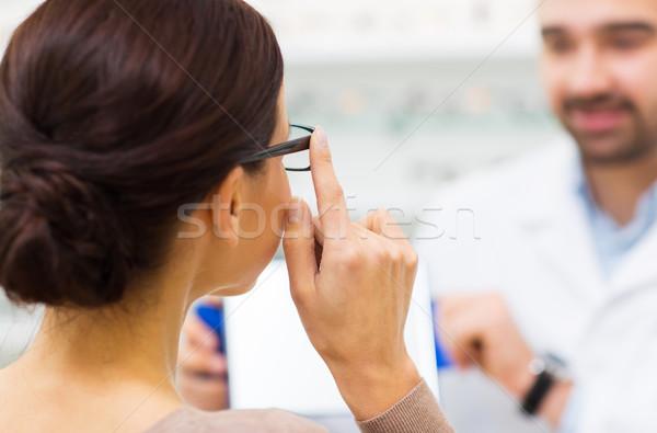 close up of woman choosing glasses at optics store Stock photo © dolgachov