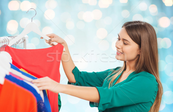 happy woman choosing clothes at wardrobe Stock photo © dolgachov