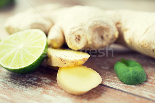 close up of ginger root and lime on wooden table Stock photo © dolgachov