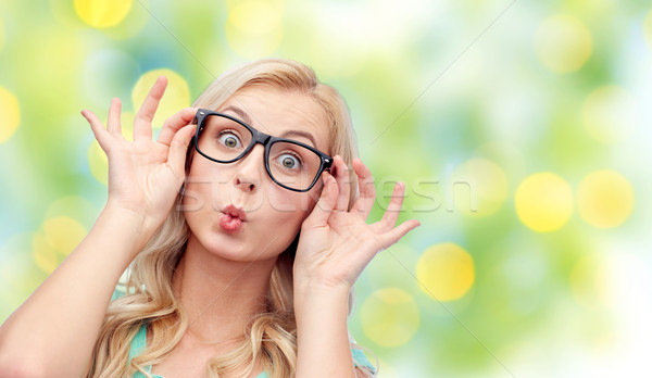 happy young woman in glasses making fish face Stock photo © dolgachov