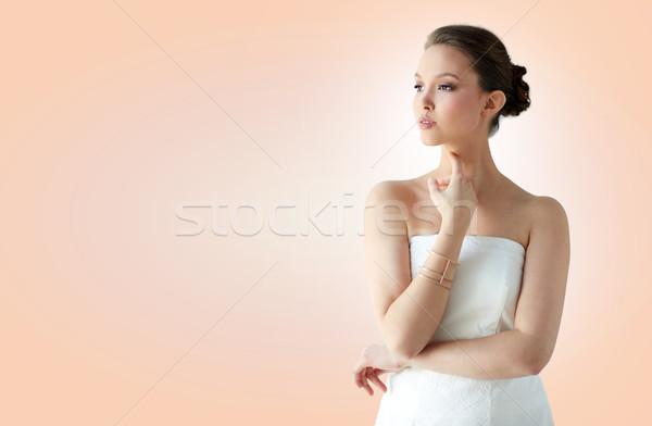 Gyönyörű ázsiai nő arany karkötő szépség Stock fotó © dolgachov