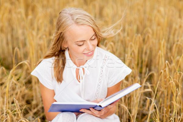 Sorridente mulher jovem leitura livro cereal campo Foto stock © dolgachov