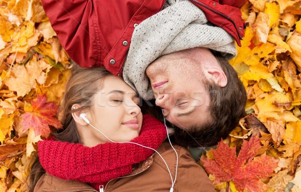 close up of smiling couple lying in autumn park Stock photo © dolgachov