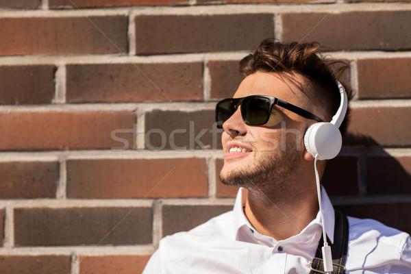 young man in headphones over brickwall Stock photo © dolgachov