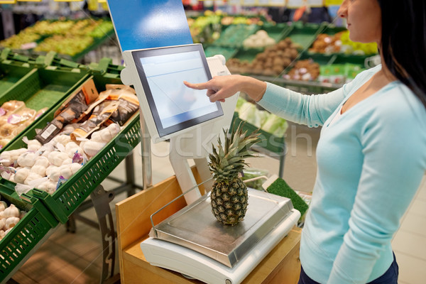 woman weighing pineapple on scale at grocery store Stock photo © dolgachov