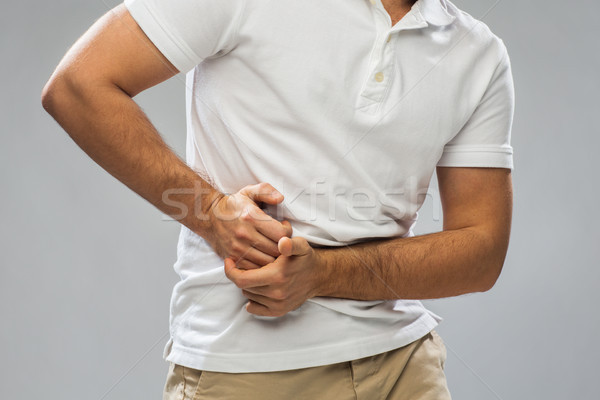 close up of man suffering from stomach ache Stock photo © dolgachov