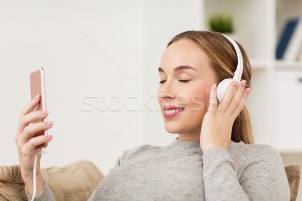 woman with smartphone and headphones at home Stock photo © dolgachov