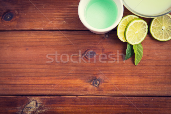 Stock photo: close up of body lotion, cream and limes on wood