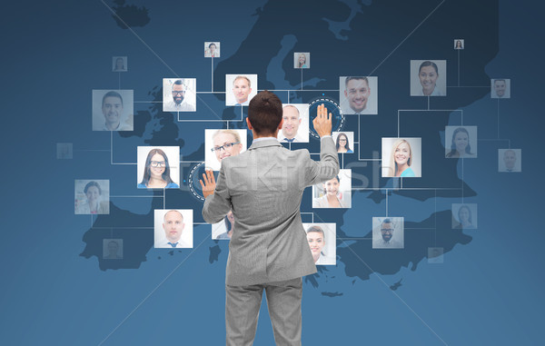 businessman using virtual screen with contacts Stock photo © dolgachov
