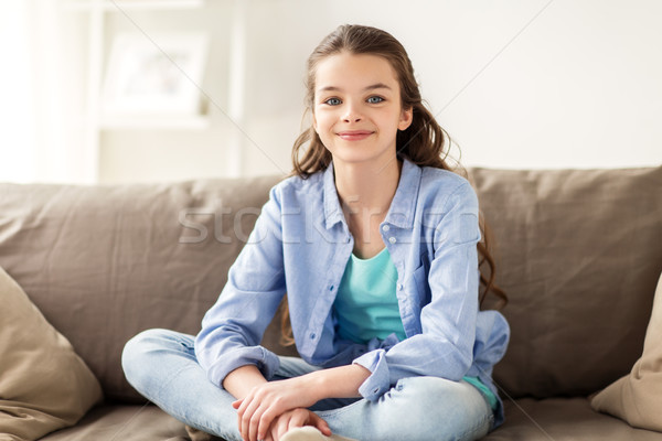 happy smiling preteen girl sitting on sofa at home Stock photo © dolgachov