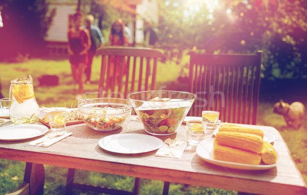 people coming to table with food at summer garden Stock photo © dolgachov