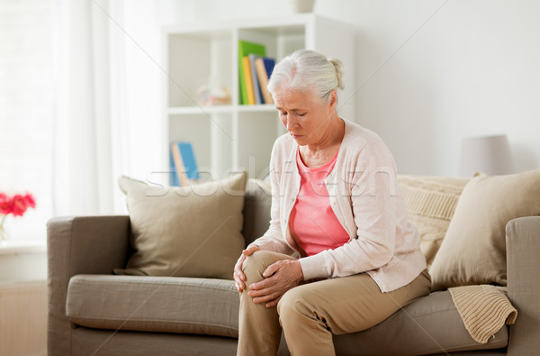 senior woman suffering from pain in leg at home Stock photo © dolgachov