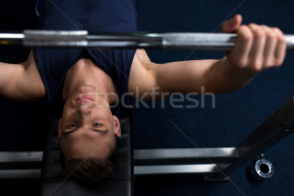 young man flexing muscles with bar in gym Stock photo © dolgachov