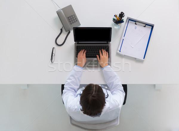Mujer médico escribiendo portátil clínica medicina Foto stock © dolgachov