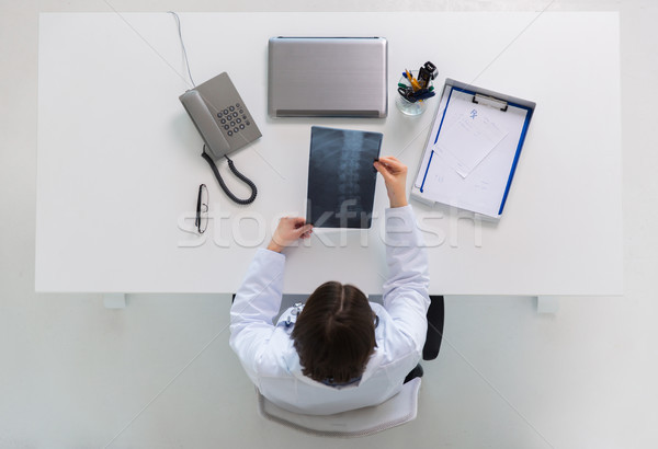 doctor with spine x-ray sitting at table Stock photo © dolgachov