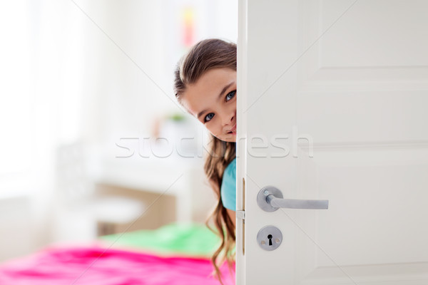 happy smiling beautiful girl behind door at home Stock photo © dolgachov