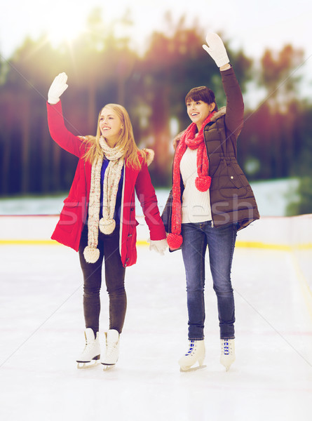 women or friends waving hands on skating rink Stock photo © dolgachov