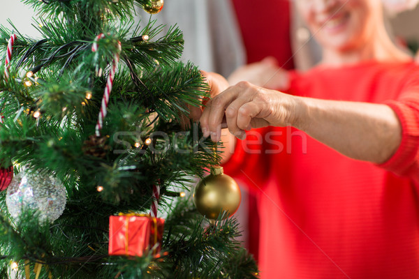 close up of senior woman decorating christmas tree Stock photo © dolgachov