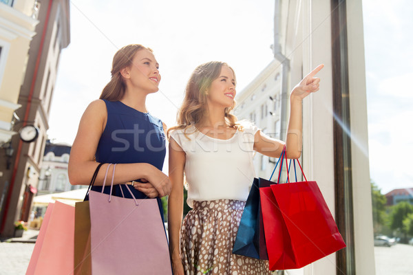 happy women with shopping bags at storefront Stock photo © dolgachov