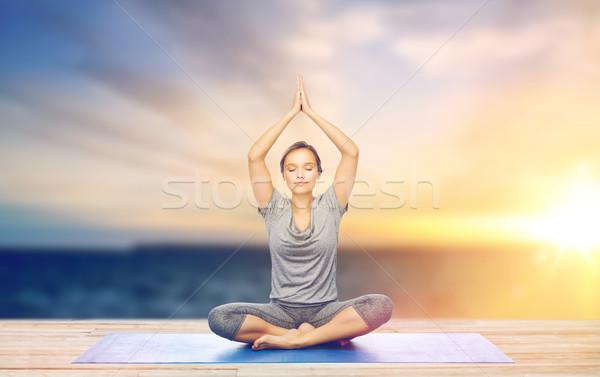woman meditating in lotus pose on mat outdoors Stock photo © dolgachov