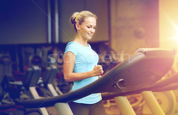 Mosolygó nő testmozgás futópad tornaterem sport fitnessz Stock fotó © dolgachov