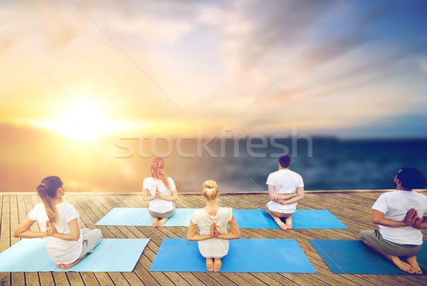 group of people doing yoga outdoors Stock photo © dolgachov