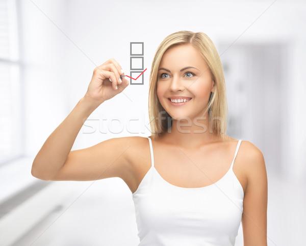 woman in white shirt drawing red checkmark Stock photo © dolgachov