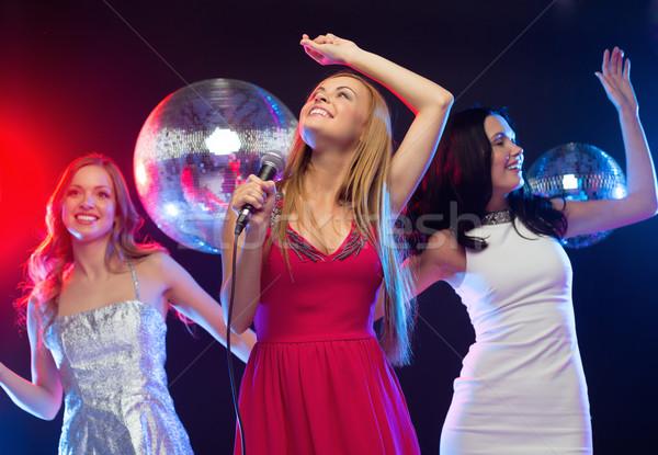 Stock photo: three smiling women dancing and singing karaoke