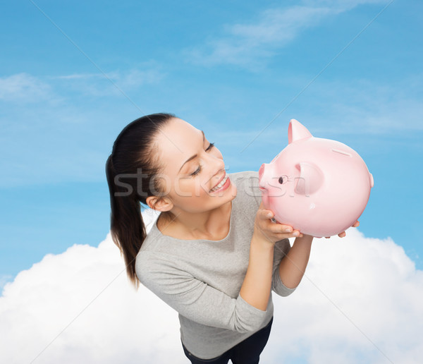 happy woman looking at piggy bank Stock photo © dolgachov
