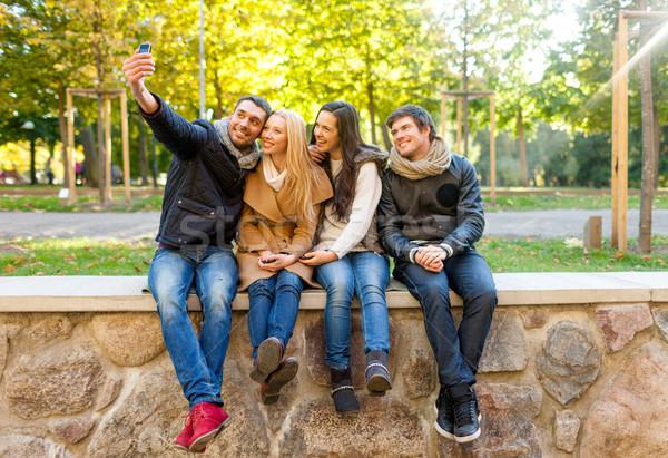Glimlachend vrienden smartphones stad park reizen Stockfoto © dolgachov