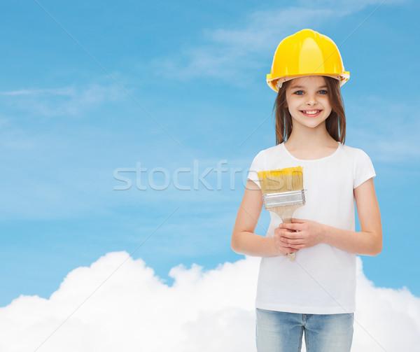 Souriant petite fille casque pinceau peinture bâtiment Photo stock © dolgachov