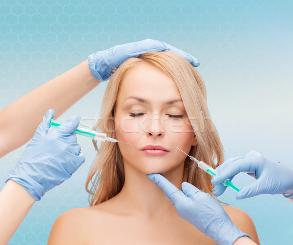 Stock photo: woman face and beautician hands with syringes