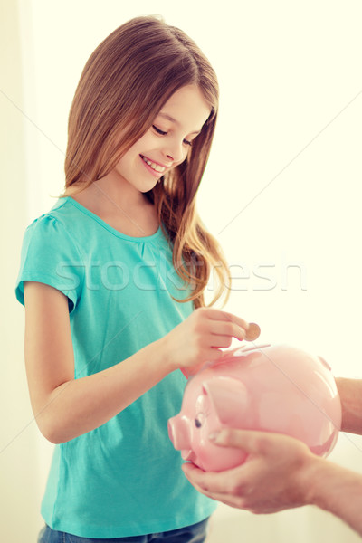 smiling little girl putting coin into piggy bank Stock photo © dolgachov