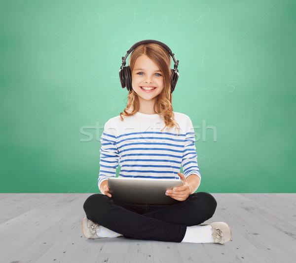 happy school girl with headphones and tablet pc Stock photo © dolgachov