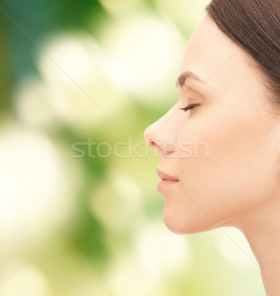 beautiful young woman face over green background Stock photo © dolgachov