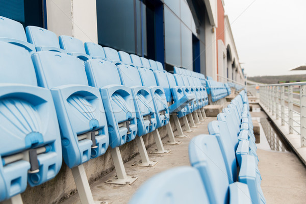 rows with folded seats of bleachers on stadium Stock photo © dolgachov