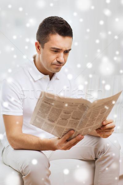 sad man reading newspaper at home Stock photo © dolgachov