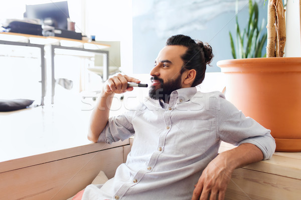 Stock photo: smiling man with beard and hair bun at office
